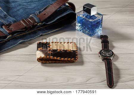 Man perfume watch with a leather strap jeans with leather belt and leather purse on a gray wooden background