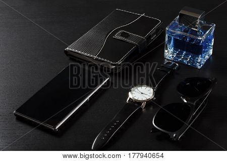 Watch with a leather strap notebook in leather cover sell phone man perfume sunglasses on a black background