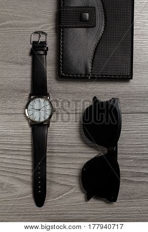 Watch with a leather strap notebook in leather cover black sunglasses on a gray wooden background