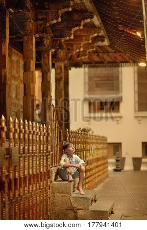 In the temple of a buddha's tooth, a small barefoot boy sits on the porch