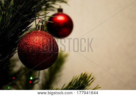 Christmas card. Christmas. New Year. Two red ball, fir-tree toy on the Christmas tree. on a light background. Bright lights.