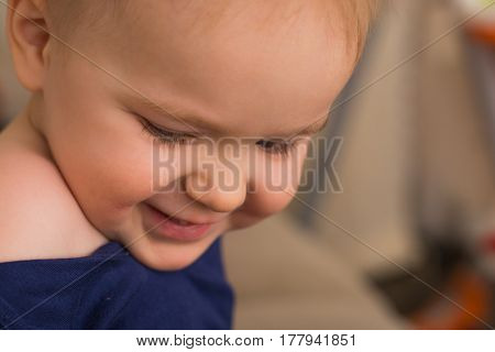 Beautiful happy little caucasian boy (white) 2-3 years close-up looking down and smiling