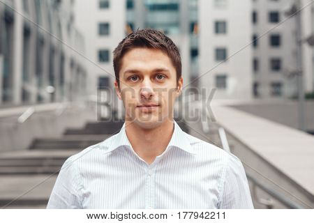 Portrait of an handsome businessman against the background of the business center. Young man in an urban setting.