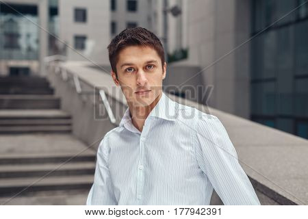 Young business man looking at camera and smiling. Young man in white shirt standing near the business center.