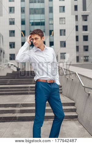 Young business man posing on camera. Model pose on the background of office building business center.