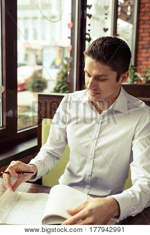 Businessman freelancer working with documents in a cafe. Young man dressed formal with notebook and pen.