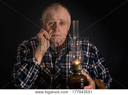 Low key portrait of senior man taking an old kerosene lamp in darkness