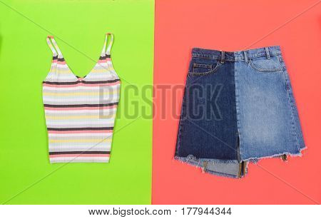 Blue denim skirt with shirt isolated on green and orange background