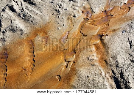 Wet sand and orange rust pollution background