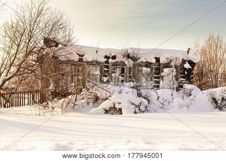 Old abandoned wooden house ruins winter, Russia