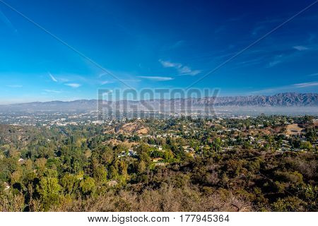 View of distant mountains and neighborhoods from Mulholland Drive, Los Angeles, California, USA.