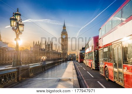 London England - The iconic Big Ben and the Houses of Parliament with lamp post and famous red double-decker buses on Westminster bridge at sunset with blue sky