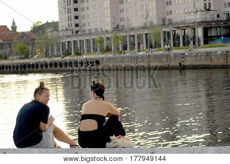 Oslo Norway - July 22 2014: girls sitting on embankment and looking on Bjorvika bay near Opera house