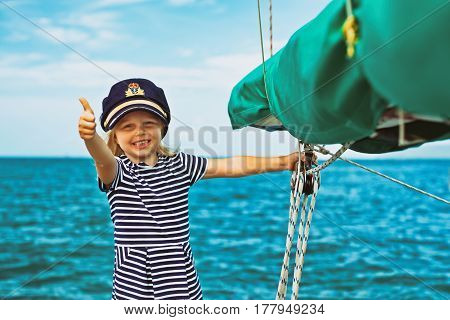 Vintage style. Happy little baby captain on board of sailing yacht watching sea on summer cruise. Travel adventure yachting with child on family vacation. Kid sailor clothing nautical fashion.