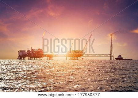 Offshore construction platform for production oil and gas in gulf of Thailand with sunset sky