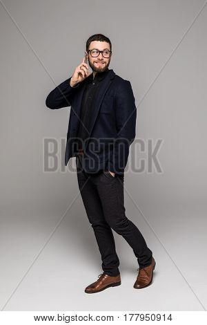 Full Height Young Serious Bearded Businessman Talking Of Phone With Colleague