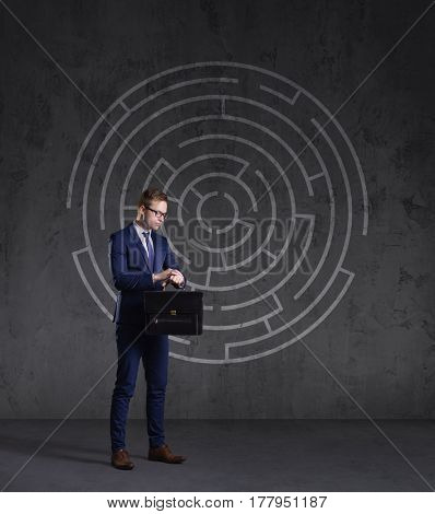 Businessman with briefcase standing on a labyrinth background. Business, strategy, concept.