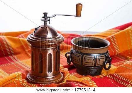 Ceramic mug with grinder on decorative tablecloth.