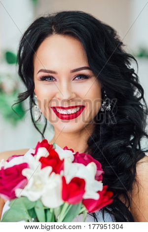 gorgeous bride with fashion makeup and hairstyle in a luxury wedding dress . Red lips