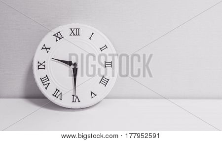 Closeup white clock for decorate show half past nine o'clock or 9:30 a.m. on white wood desk and wallpaper textured background in black and white tone with copy space