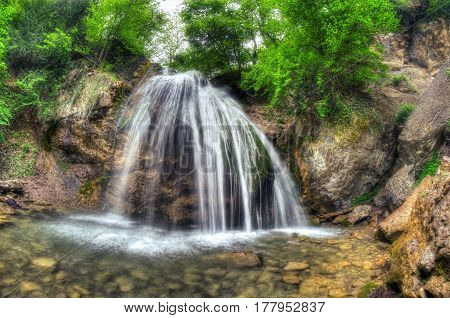 Beautiful Waterfall On The Mountain River With Green Trees.