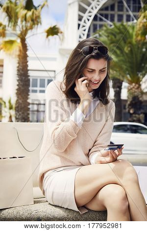 Modern city girl activating credit card on phone