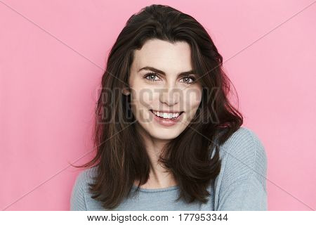 Young Brunette woman smiling against pink background
