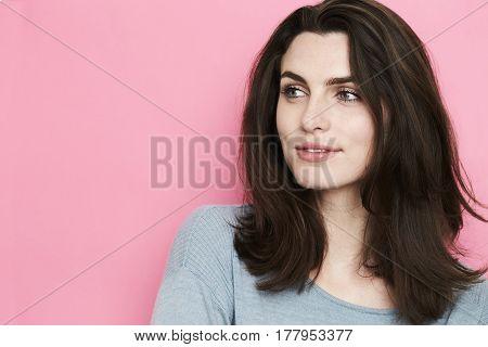 Brown haired beauty looking away in pink studio