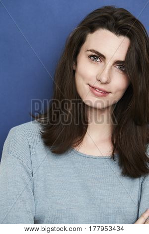 Young Beautiful woman against blue background smiling