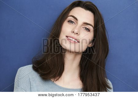 Gorgeous green eyed woman in blue studio smiling