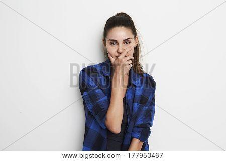 Brunette woman covering mouth in studio portrait