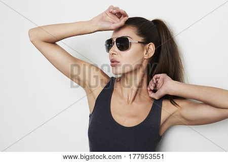 Stretching cool girl in vest and shades studio