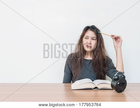 Closeup asian woman tired from reading a book with boring face emotion in work concept on wood table and white cement wall textured background with copy space