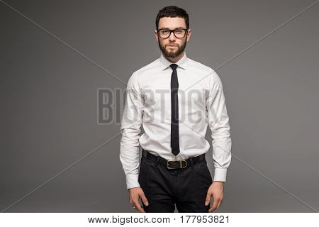 Handsome Young Businessman In White Shirt And Tie Standing And Glasses Over Grey Background