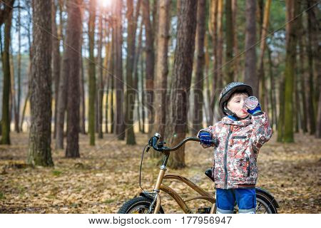 Young Boy With Bicycle With Drinking Clear Water