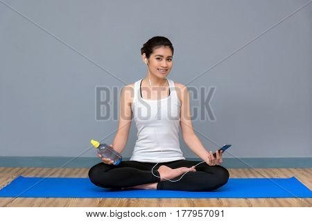 Young asian woman enjoy the music before practicing yoga at yoga healthy sport gym yoga and meditation have good benefits for health. Photo concept for Yoga Sport and Healthy lifestyle