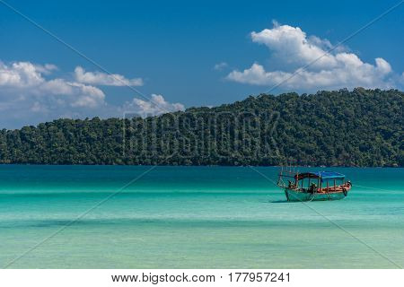Old Wooden Long Tail Boat Anchored Off The Beach In A Tropical Calm Sea With Tree Lined Headland In