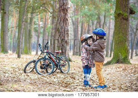 Two Little Kids Boys, Best Friends In Autumn Forest. Older Brother Helping Younger Child To Put His
