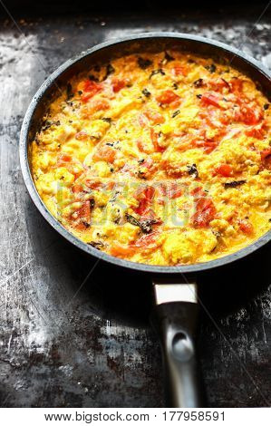 Scrambled Eggs With Tomatoes And Basilic In Black Frying Pan