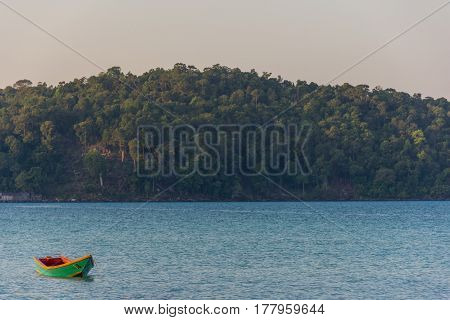 A Green Old Wooden Long Tail Boat Floats In A Calm Still Sea At Golden Hour With A Tree Lined Head L