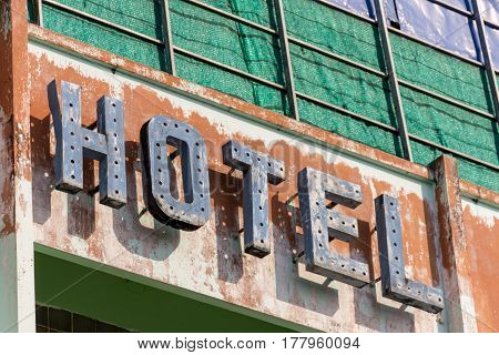 Old metal Hotel sign in need of repair attached to a wall in need of repainting.