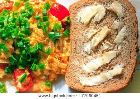 Tasty Fresh Breakfast: Scrambled Eggs With Cherry Tomatoes, Chive And A Slice Of Whole Grain Bread W