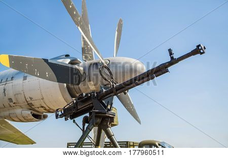 Retro gun on the tripod and optical sight against the backdrop of the aircraft propellers close-up. Machine gun outdoors.
