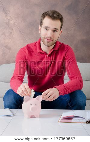 Young man puts savings into piggy bank. savings money piggybank home budget cost concept