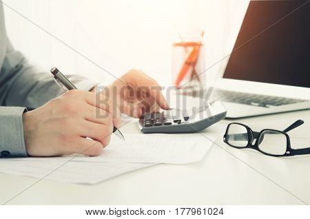 Businessman Working In Office With Calculator