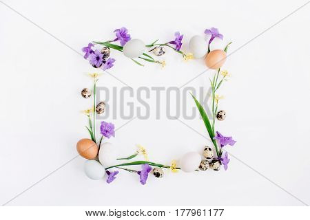Frame wreath made of Easter eggs quail eggs yellow and purple flowers on white background. Flat lay top view. Traditional spring concept. Easter concept.