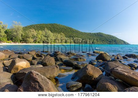 White sandy beach bay with large stones in foreground and forested headland in the distance on a tropical island.