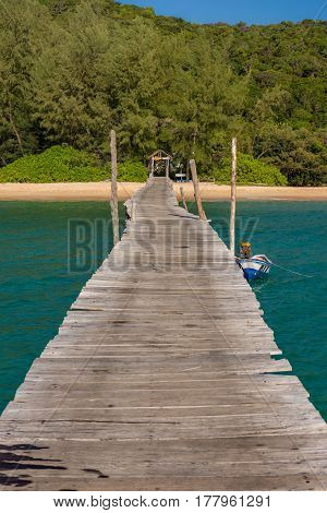 Old wooden pier leading to white sand beach lined with dense forest.