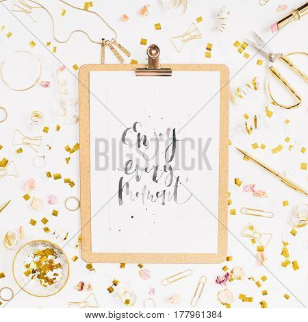 Beauty blog background. Quote Enjoy Every Moment clipboard and gold style feminine accessories pattern. Golden tinsel scissors pen rings necklace bracelet on white background. Flat lay top view.