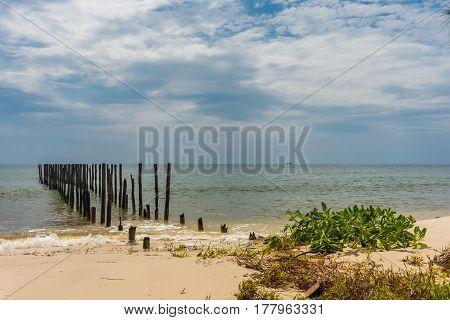2 Rows Of Wooden Posts Go Out In To A Calm Paradise Sea Off Of A Beautiful Beach.